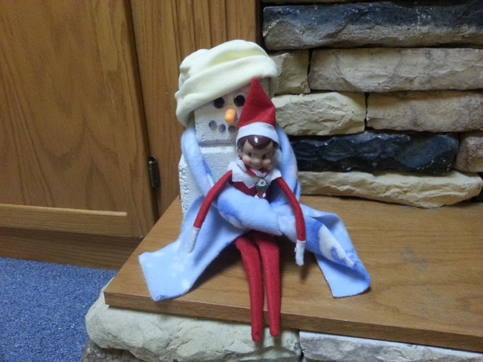Elf on the Shelf cuddling with a snowman