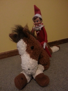 Having fun riding Snowflake, the stuffed horse.