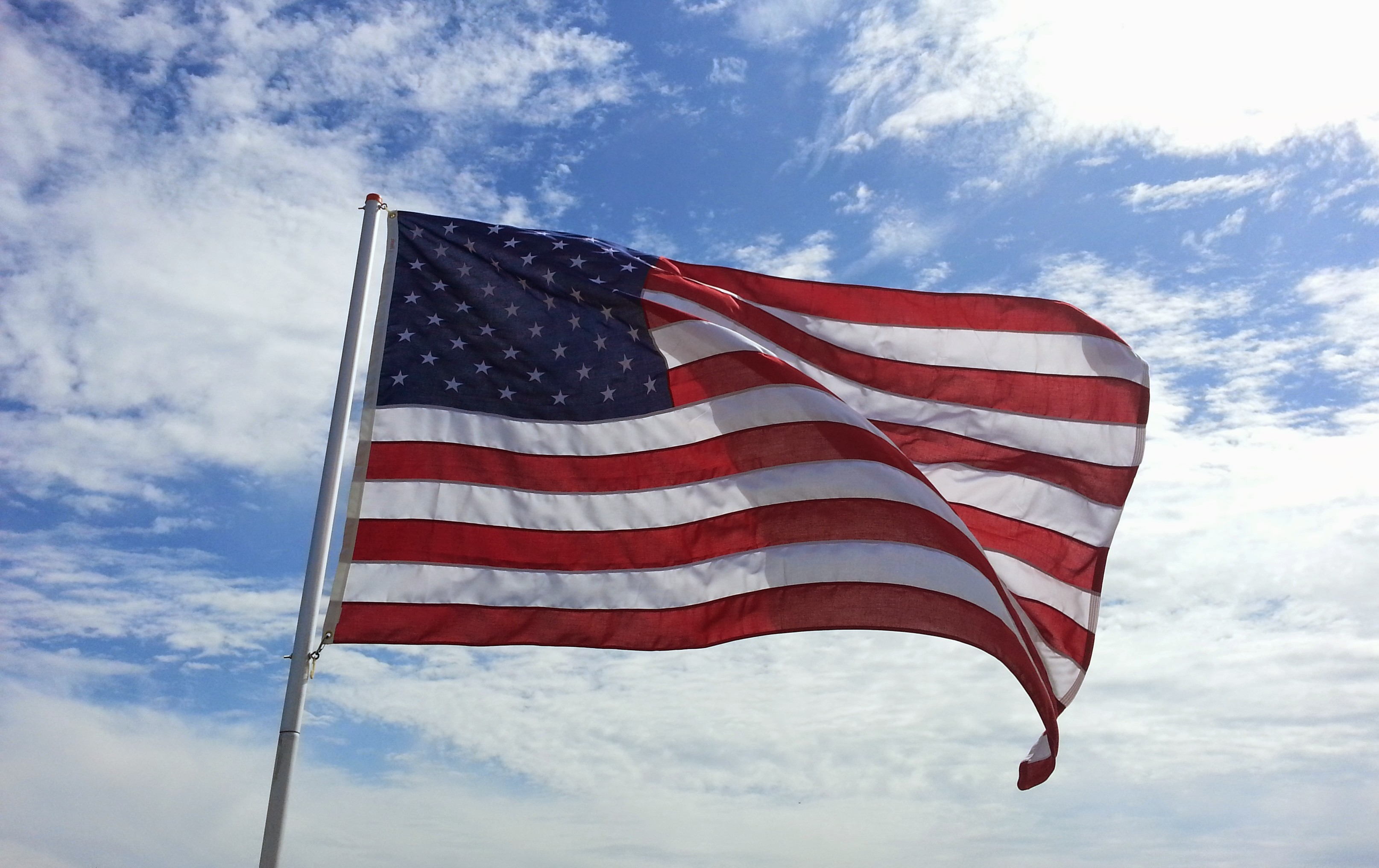 American Flag blows in the wind against  a blue sky with cloud